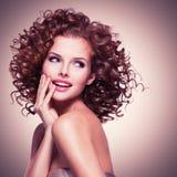 Красивая усмехаясь заботливая женщина с вьющиеся волосы стоковое фото
