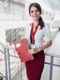 Красивая усмехаясь коммерсантка стоя против белой предпосылки офисов Портрет бизнес-леди с папкой в ее руках стоковая фотография rf