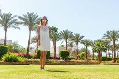 Красивая усмехаясь маленькая девочка в белых платье и шляпе в лете стоковые фотографии rf