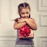 Красивая усмехаясь милая девушка держа и обнимая острословие коробки золота Стоковые Фотографии RF