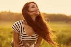 Красивая усмехаясь молодая женщина выглядя счастливый с длинными изумительными яркими длинными волосами на предпосылке лета заход стоковое фото rf