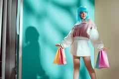 красивая усмехаясь молодая женщина в голубом бумажном мешке удерживания парика стоковые изображения