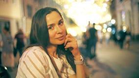 Красивая усмехаясь молодая женщина против загоренной предпосылки пешеходной зоны сток-видео