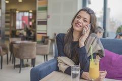 Красивая усмехаясь молодая женщина сидя внутри помещения и говоря на толпе Стоковое Изображение