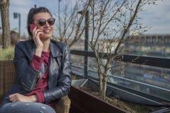 Красивая усмехаясь молодая женщина сидя outdoors и говоря на мобильном телефоне Стоковые Фото