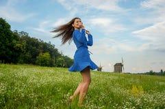 Красивая усмехаясь молодая женщина танцует и завихряется в голубом Д-р Стоковое Фото