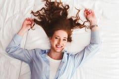 Красивая усмехаясь молодая красная женщина волос кладя в кровать Стоковое Фото
