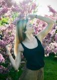 Красивая усмехаясь молодая женщина около blossoming дерева весны Портрет довольно белокурой девушки с длинными волосами в розовых Стоковые Фотографии RF