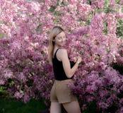 Красивая усмехаясь молодая женщина около blossoming дерева весны Портрет довольно белокурой девушки с длинными волосами в розовых Стоковые Изображения RF