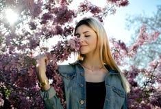 Красивая усмехаясь молодая женщина около blossoming дерева весны Портрет довольно белокурой девушки с длинными волосами в розовых Стоковые Фото