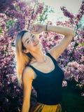 Красивая усмехаясь молодая женщина около blossoming дерева весны Портрет довольно белокурой девушки с длинными волосами в розовых Стоковая Фотография