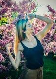 Красивая усмехаясь молодая женщина около blossoming дерева весны Портрет довольно белокурой девушки с длинными волосами в розовых Стоковое фото RF