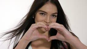 Красивая усмехаясь предназначенная для подростков девушка делает форму сердца с ее руками акции видеоматериалы