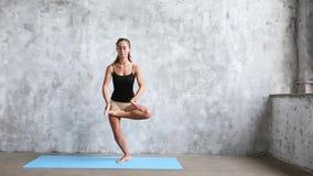 Красивая усмехаясь разминка женщины внутри помещения, делающ тренировку йоги на голубой циновке видеоматериал