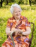 Красивая усмехаясь старуха сидя в стуле Стоковое фото RF