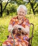 Красивая усмехаясь старуха сидя в стуле Стоковое Фото