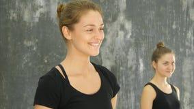 Красивая усмехаясь счастливая молодая женщина разрабатывая внутри помещения, стоя и говоря к группе Стоковые Фото
