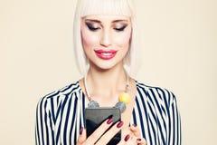 Красивая усмехаясь фотомодель женщины смотря мобильный телефон Стоковые Фото