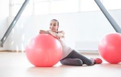Красивая услаженная склонность женщины на шарике фитнеса Стоковое Фото