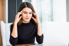 Красивая утомленная бизнес-леди держит eyeglasses и массажирует пока работающ в офисе стоковое изображение