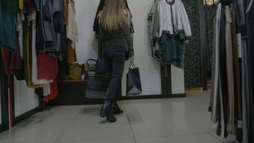 Красивая ученица колледжа идя в высокие пятки держа хозяйственные сумки в моле магазина одежды - сток-видео