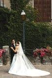 Красивая французская невеста в длинном платье обнимая в старых лозах улицы Стоковая Фотография