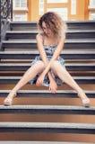 Красивая хорошо выхоленная женщина в голубом платье сидя на лестницах Вьющиеся волосы покрывает ее сторону стоковое изображение