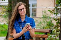 Красивая худенькая девушка в стеклах сидит на стенде в парке Стоковые Фотографии RF