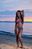 Красивая черная Афро-американская женщина представляя на пляже на su стоковое изображение