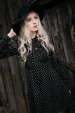 Красивая черная шляпа привлекательной и стильной девушки нося стоя представляющ в городе Обнажённый состав, наиболее хорошо ежедн Стоковые Фото
