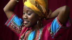 Красивая чернокожая женщина в традиционных африканских одеждах представляя в студии, замедленном движении сток-видео