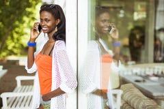 Красивая чернокожая женщина говоря на телефоне и усмехаться Стоковое Фото