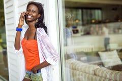 Красивая чернокожая женщина говоря на телефоне и усмехаться Стоковая Фотография RF