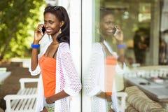 Красивая чернокожая женщина говоря на телефоне и усмехаться Стоковые Фотографии RF