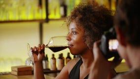 Красивая чернокожая женщина на фотосессии в баре Она выпивает вино и смех видеоматериал