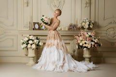 Красивая чувственная блондинка девушки в улыбках бежевого платья нежных в интерьере Стоковая Фотография