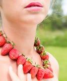 Красивая шея женщины при красные шарики сделанные из свежей клубники стоковая фотография