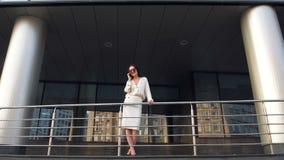 Красивая элегантная коммерсантка брюнет с мобильным телефоном говоря, усмехаясь и смеясь над перед зданием небоскреба видеоматериал