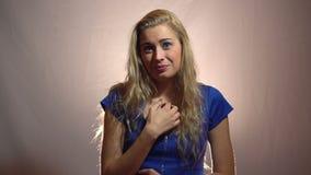 Красивая эмоциональная белокурая девушка в голубом платье чувствует виновной в студии с светлой предпосылкой сток-видео