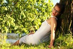 Красивая эмоциональная девушка в белом платье лежа на траве мимо Стоковые Фотографии RF