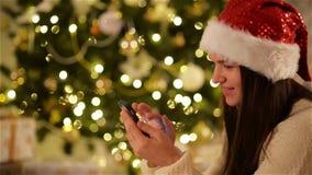 Красивая эмоциональная девушка в шляпе Санты используя устройство рядом с рождественской елкой Усмехаясь женщина с Smartphone на
