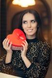 Красивая элегантная женщина держа подарок формы сердца Стоковые Изображения