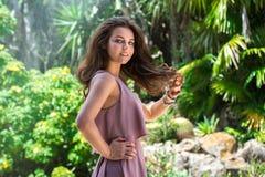 Красивая элегантная женщина представляя outdoors на зеленой тропической предпосылке леса стоковая фотография