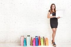 Красивая элегантная женщина стоя рядом с хозяйственными сумками пока hol Стоковые Фото