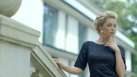 Красивая элегантная кавказская женщина в черном платье идя вверх по лестницам вне здания видеоматериал