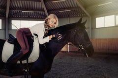 Красивая элегантная молодая белокурая девушка лежит на ее рубашке блузки черной конкуренции формы шлихты лошади белой и коричневы Стоковые Фото