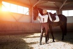 Красивая элегантная молодая белокурая девушка стоя около ее конкуренции формы шлихты лошади Стоковые Фото