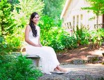 Красивая biracial невеста в белом платье свадьбы шнурка сидя дальше стоковые фотографии rf