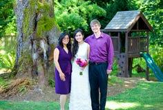 Красивая biracial невеста стоя с ее родителями разнообразность стоковое фото