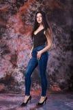 Красивая Curvy женщина представляя в черных рубашке и джинсах на пестротканой предпосылке Испытание добавочного размера модельное Стоковое Фото